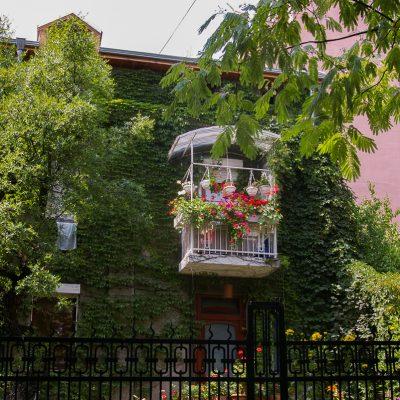 Зелена къща с бяло балконче